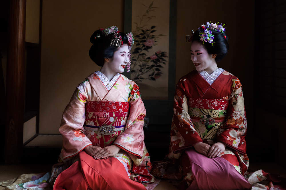 Two maiko geisha sitting in a room in Kyoto, Japan