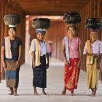 Myanmar – People – Burmese women carrying bowls of rice to the monastery