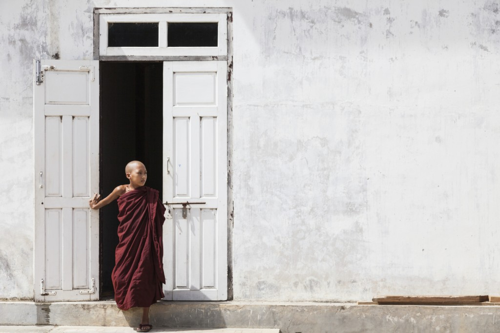 young monk standing by a door