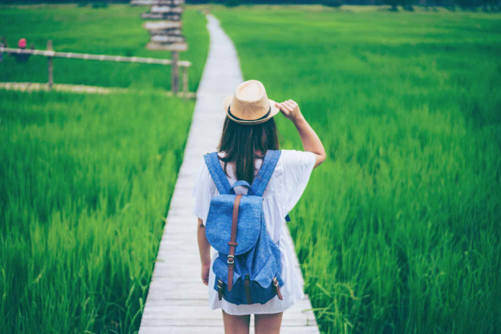 Young woman traveler with backpacker and hat standing at old white wooden bridge in rice fields.