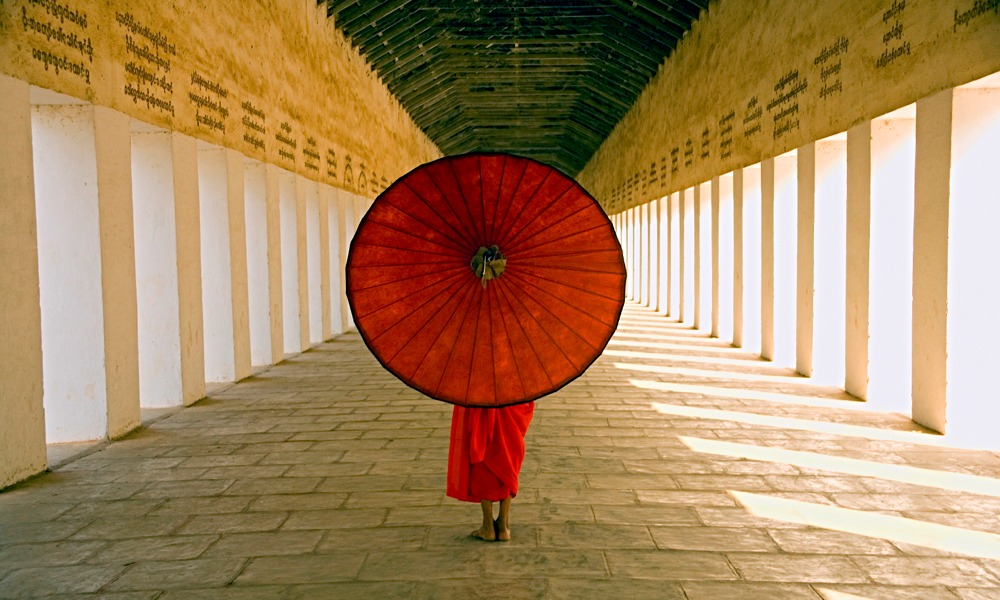 Myanmar Visa: Monk with a red umbrella in Bagan