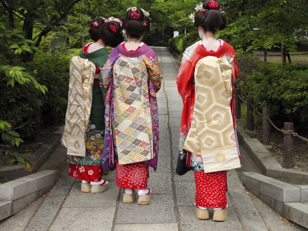 Three geishas weaing kimonos in a traditional street of Kyoto,Japan