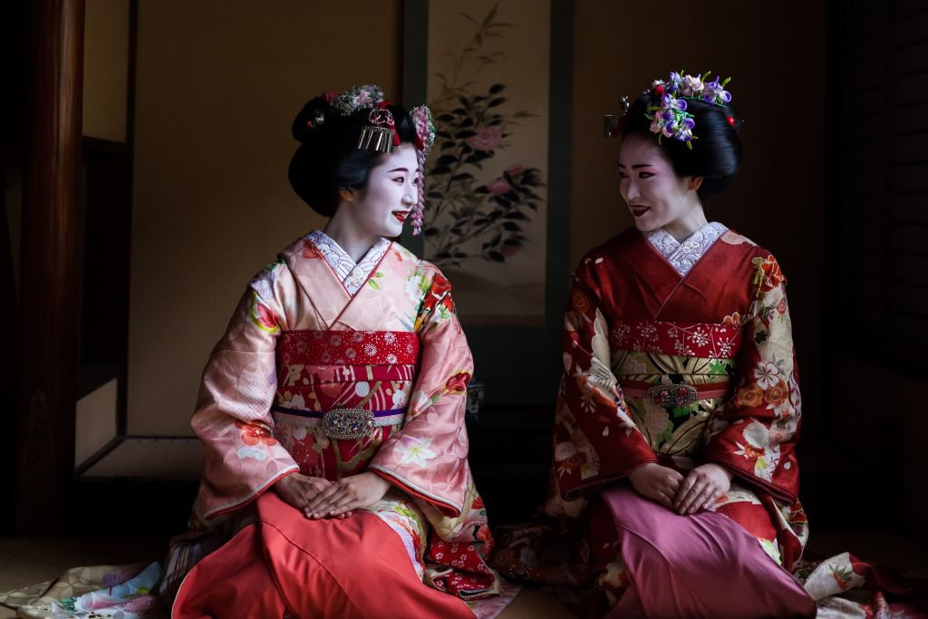 Two maiko geisha sitting next to each other in a room of a Japanese house, Kyoto, Japan