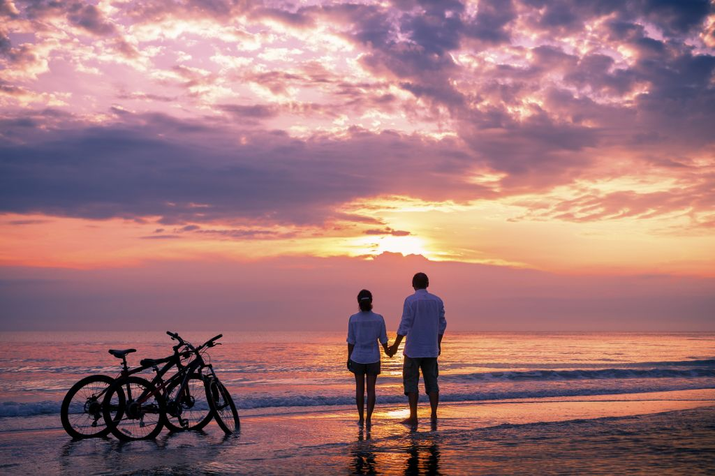 Couple biking and standing next to the beach in Thailand