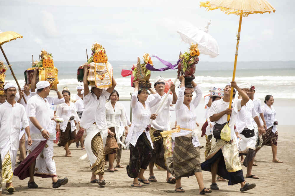 Indonesia Bali a procession of people сarrying religious offerings on the Seminyak beach for Melasti festival