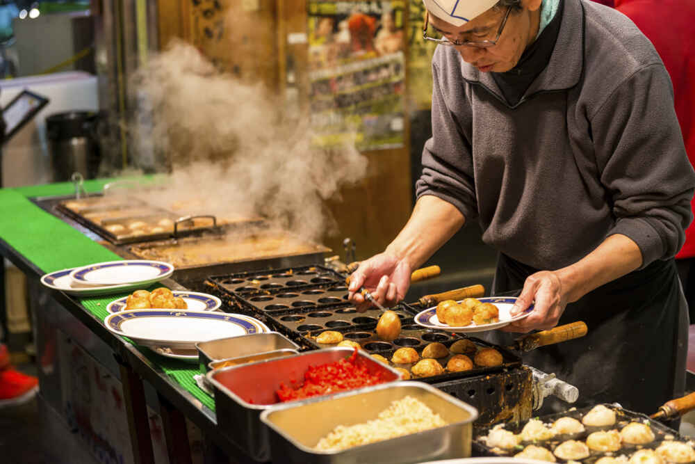 A Japanese man grills takoyaki at a food stall