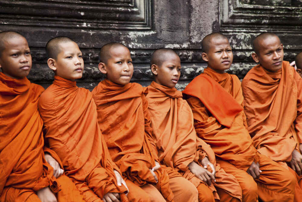 A group of cambodian buddhist monks sit in the grounds of the Ancient Angkor Wat Temples