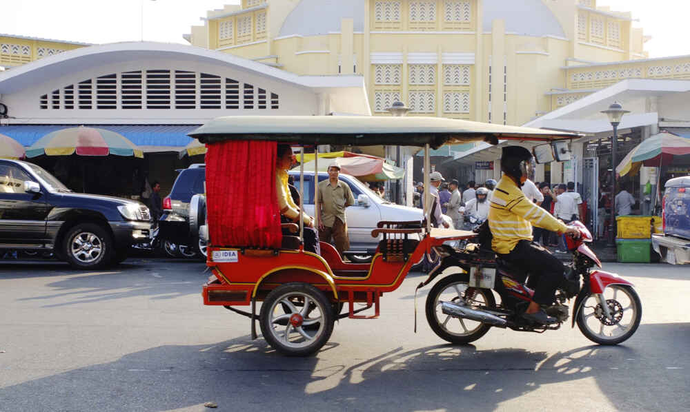 A tuk tuk driver carrying his customer and her shopping in Phnom Penh Cambodia