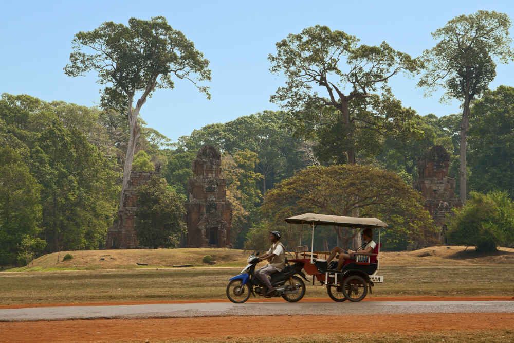 Angkor Thom Cambodia A traveler goes by a tuk tuk visiting the ancient city of Angkor Thom