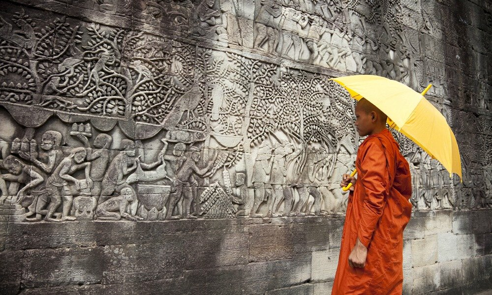 Cambodia and Vietnam Tour: monk standing in front of religious carving plate at Angkor Wat