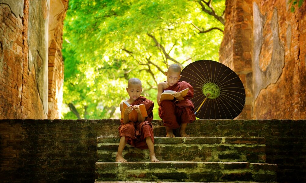 Myanmar family holiday: two children monks reading a book seated on the stairs