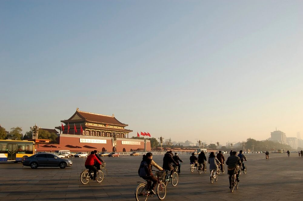 Tourists ride bike in front of Forbidden city in Beijing