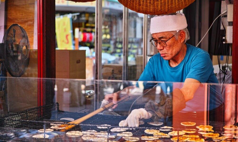 honeymoon in Japan: local Japanese man making snacks