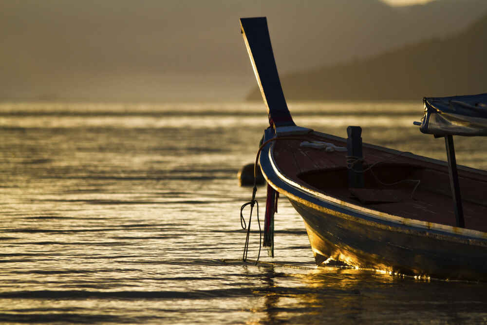 Fishing boat floating on the sea in the morning with golden light