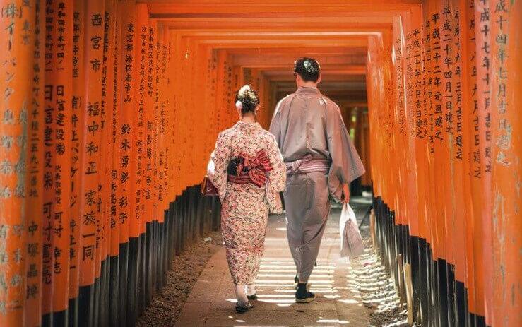 honeymoon activities in Japan: Japanese couple walking through Torii gate