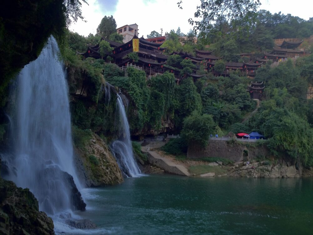 Hunan China tour: Furongzhen area with waterfall and  houses on the mountains