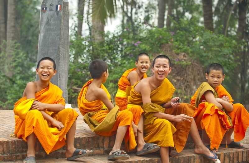 Grand tour of Indochina: happy monks smiling and laughing