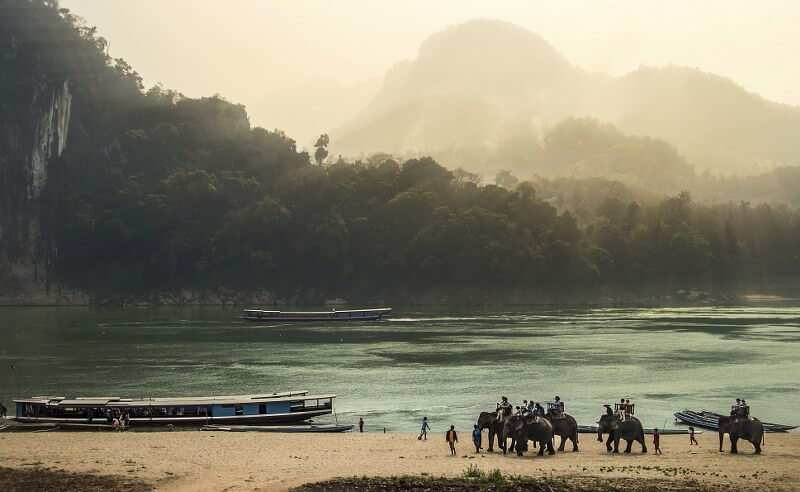 Grand tour of Indochina: elephants along the river with boats