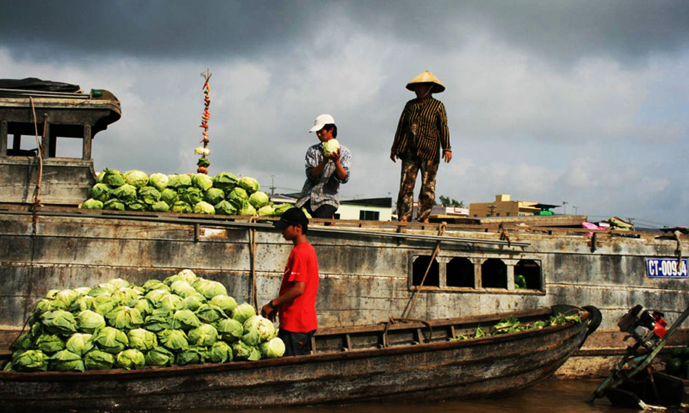 3-Night Mekong Delta Cruise: locals transporting goods and vegetables on wooden boats