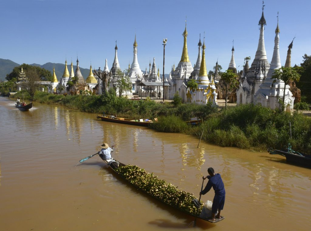 Myanmar family holiday: boat with two fisherman in Inle Lake with white pagodas on the shore