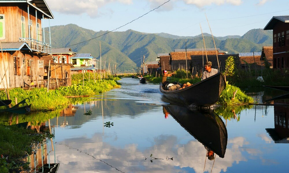 Luxury Myanmar tour: people travel by boat in a lake in Myanmar