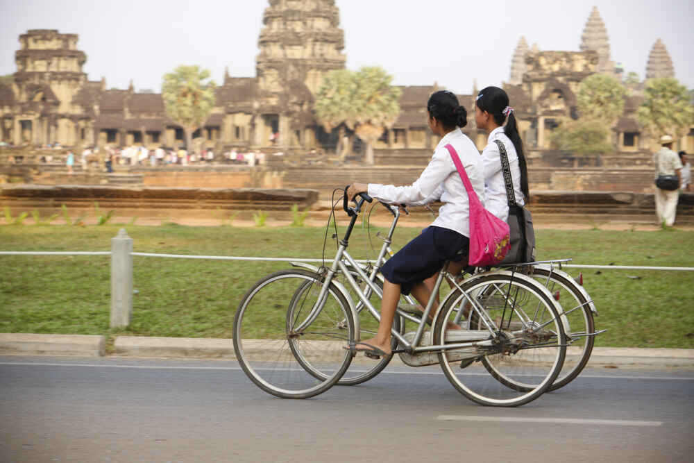 School girls ride their bikes in front of Angkor Wat Temple after school