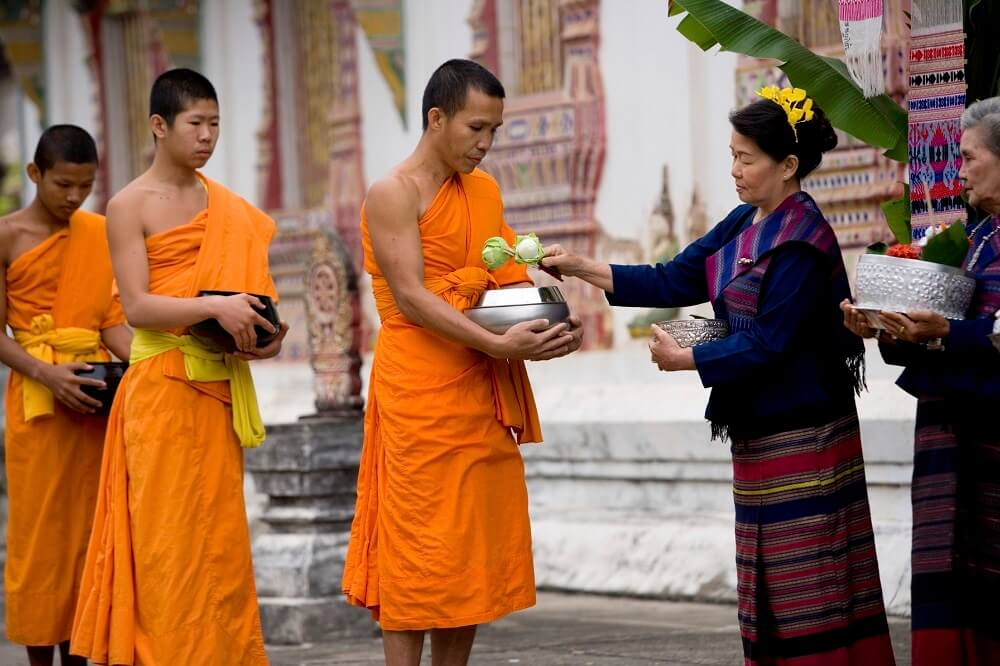 Monks in line receiving offerings from people