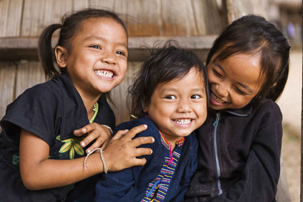 Three little girls having fun in the village in Northern Laos