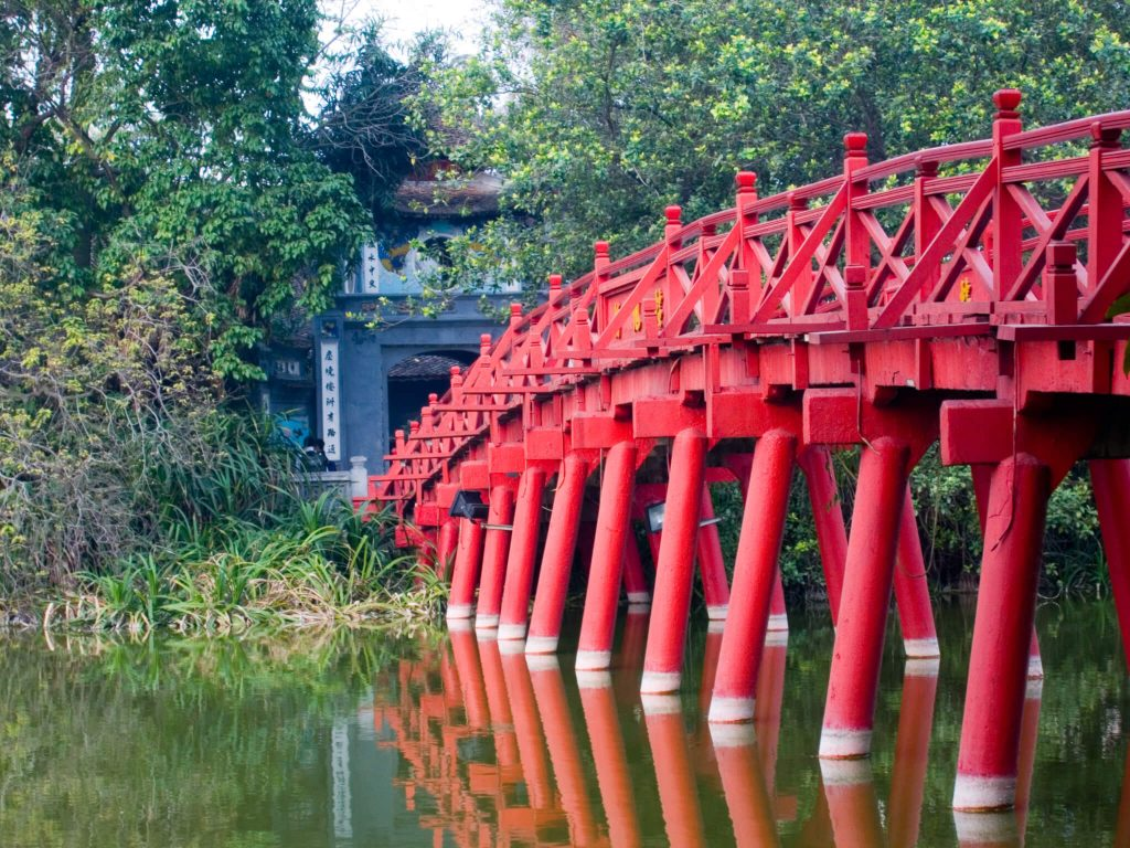 Grand tour of Indochina: red bridge crossing small, calm river