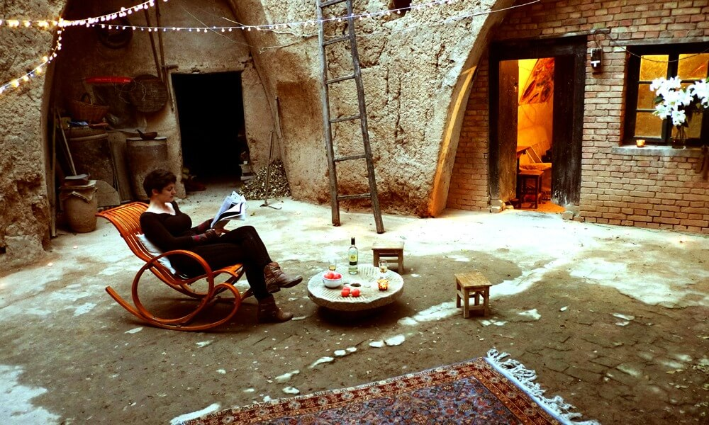 custom China tours: woman reading magazine in a cave hotel