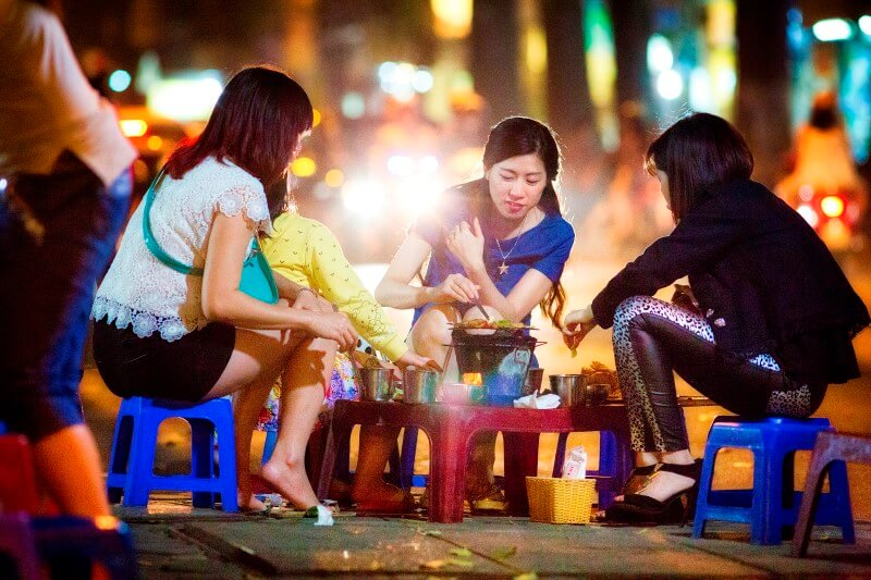 Grand tour of Indochina: a group of locals sitting and eating food on the street