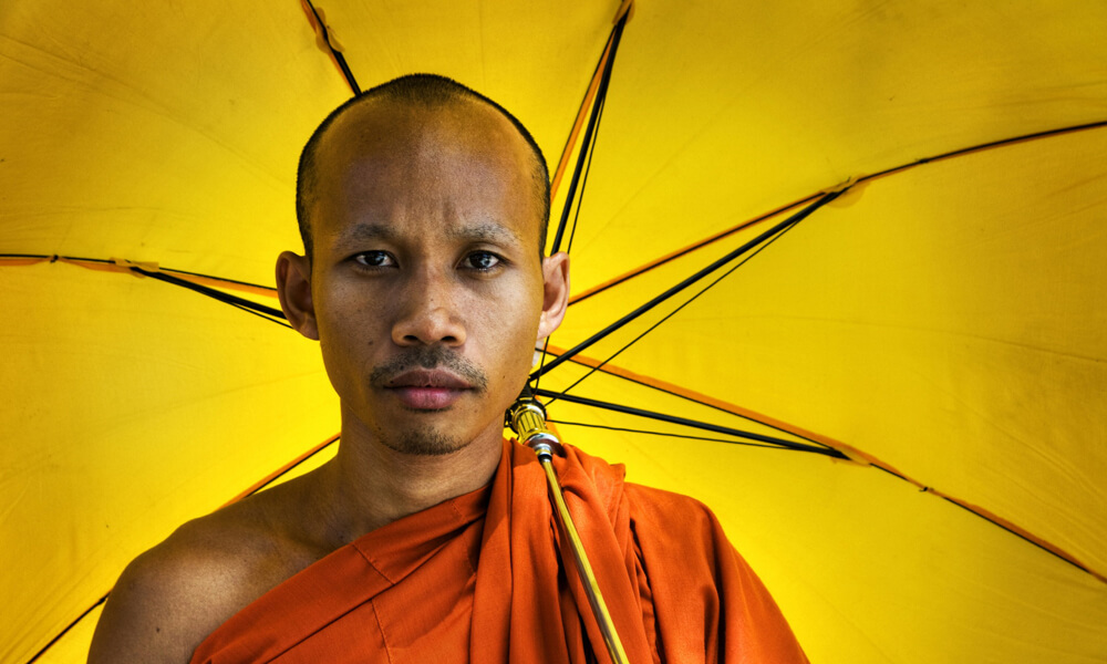 Monks with a yellow umbrella on Sustainable Cambodia tour