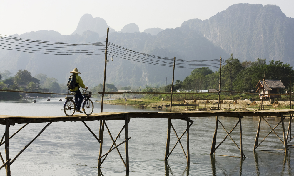 Northern Laos Tour: local biking on the bridge in Viengxay