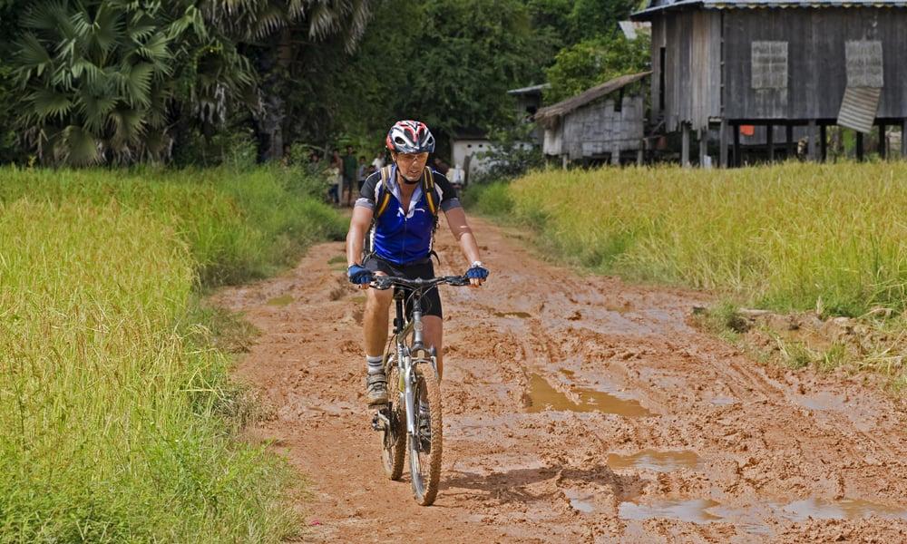 Battambang tour: men ride a bike in a dirt road