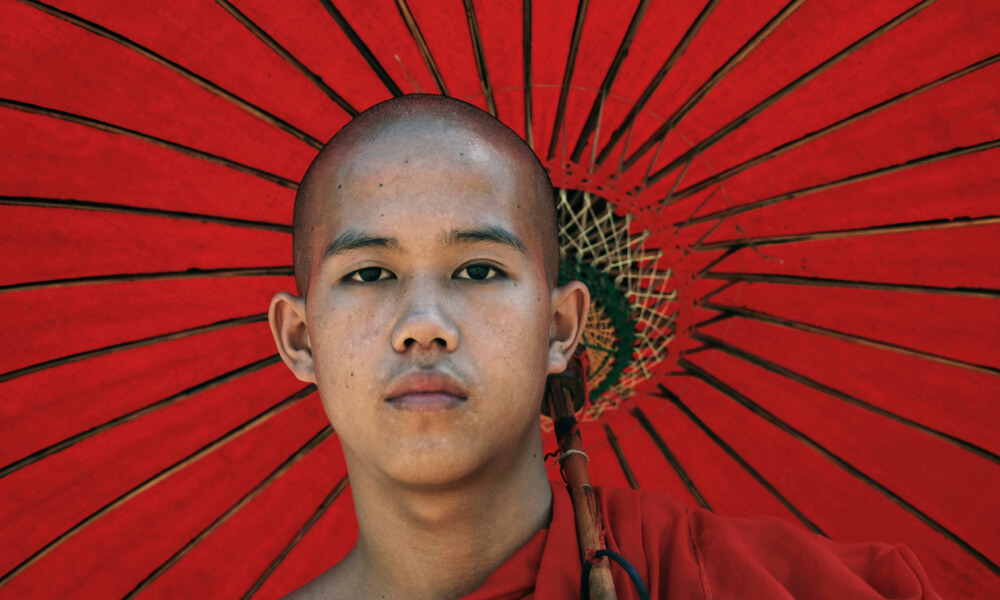 Mynamar Culinary holiday : young monk with a red umbrella
