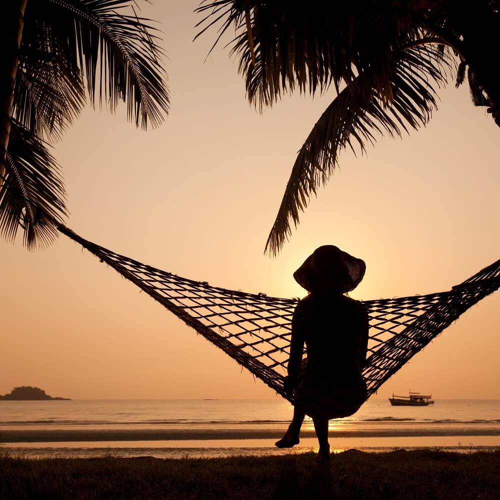 woman on a hammock looking for the sunset on dawei beach