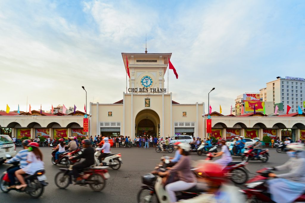 Ben Thanh market with road traffic in old town. Popular place to visit on Saigon day tour to buy handicrafts, souvenirs, try traditional Vietnamese food