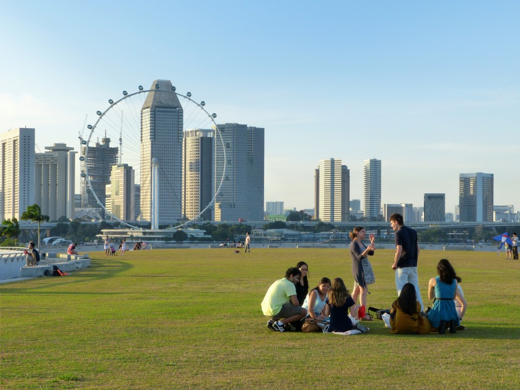 Icons of Singapore: People chilling in the park with Singapore city view with ferris wheel