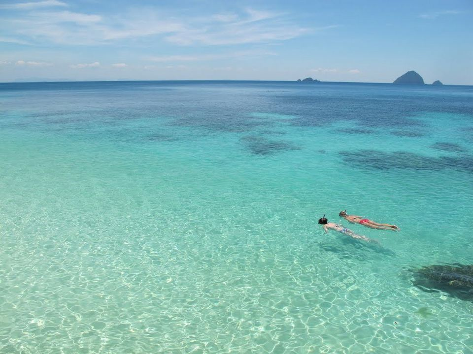 Perhentian Islands, Malaysia: couple swimming and snorkeling together in blue water honeymoon