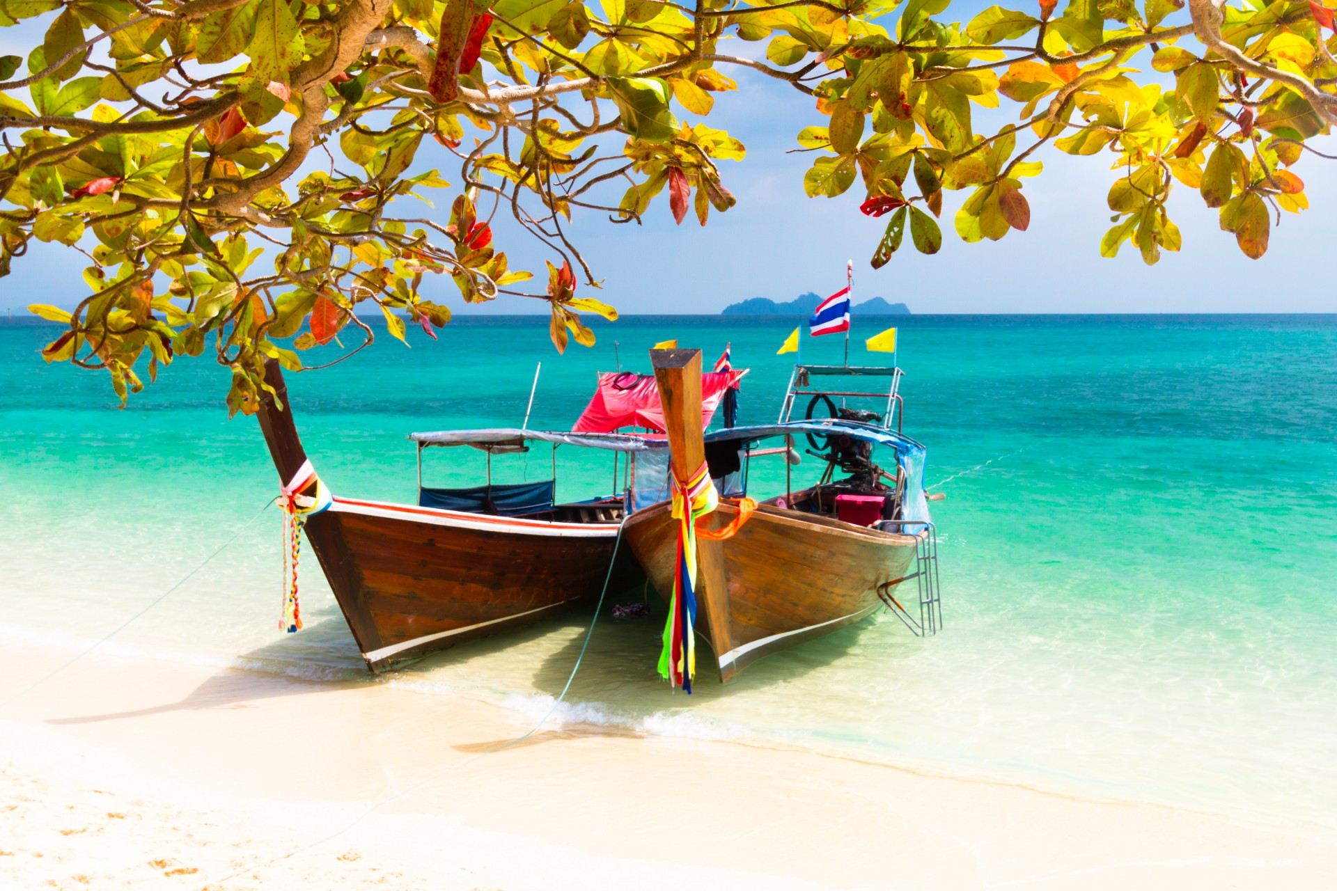 family adventure in Thailand: local wooden boats by the beach with beautiful, clear water
