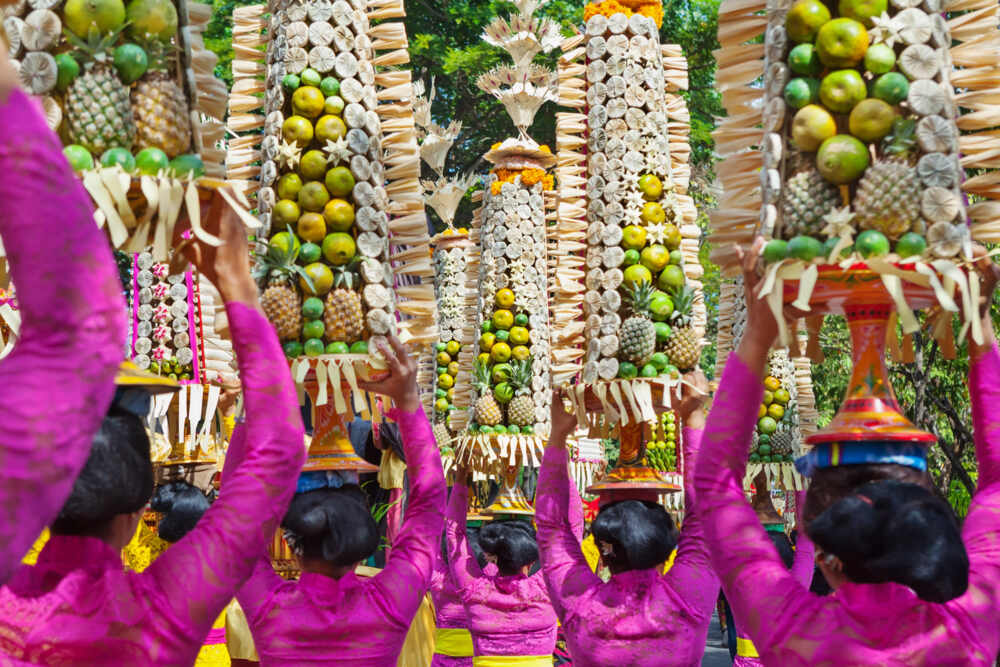 Balinese women in traditional costumes with offerings for ceremony