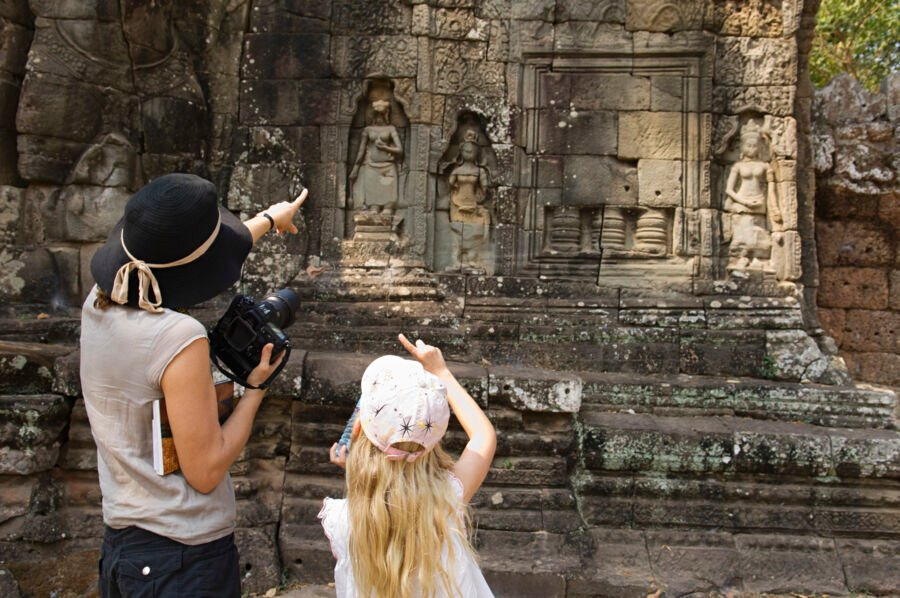 Rear view of mother and daughter pointing while looking at ancient Angkor temple during a family adventure holiday