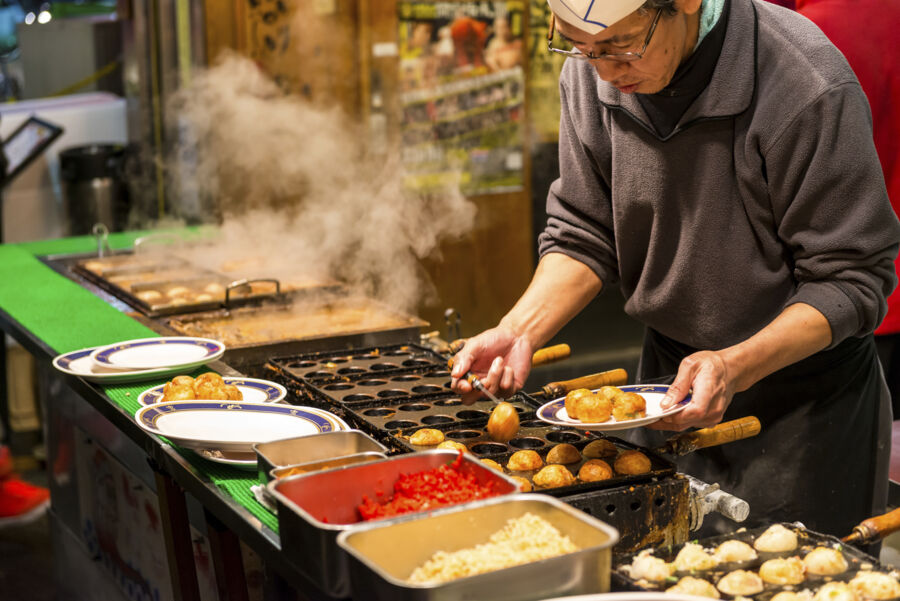 A Japanese man grills takoyaki at a food stall in Osaka
