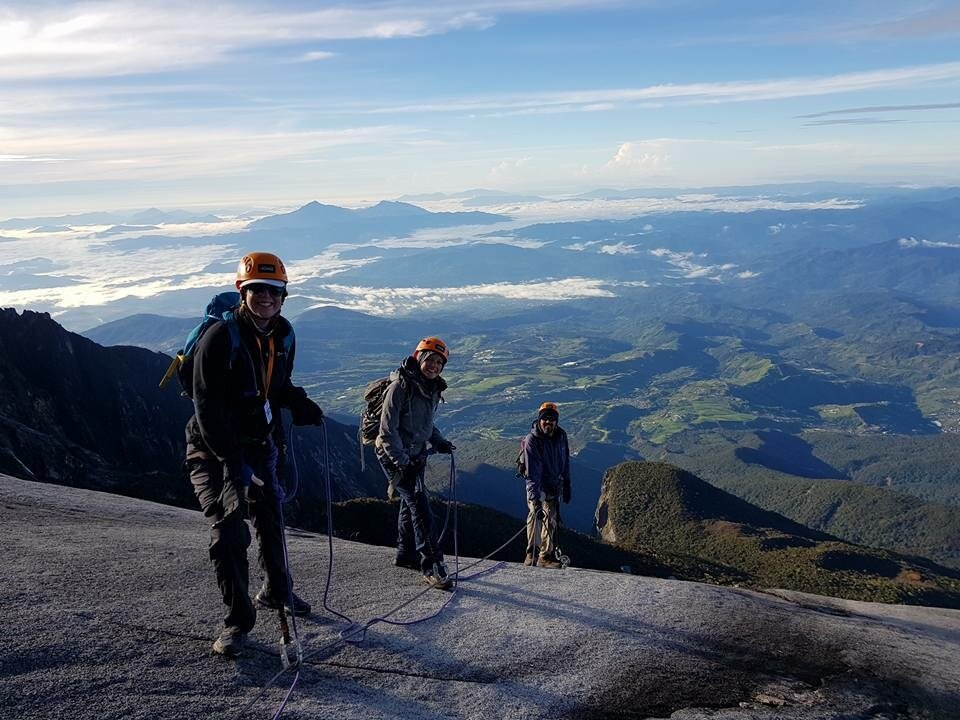 travelers asceding the Mt Kinabalu world heritage site by the via ferrata